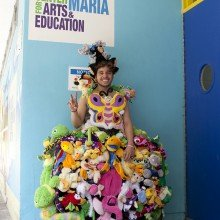 "Brian Rodriguez, wearing the ""Animal Population Decline Dress"" by Dominique Paul in front of a TatsCru mural at Casita Maria"